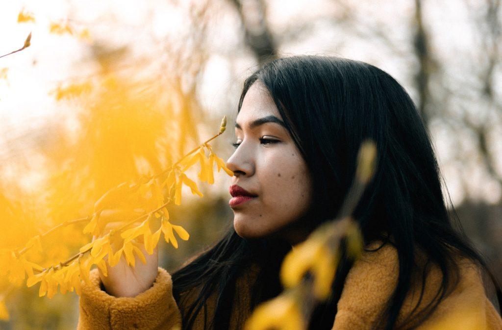 donna annusa fiori gialli